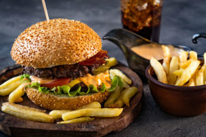 Fresh burger with crispy french fries near beverage and sauce boat