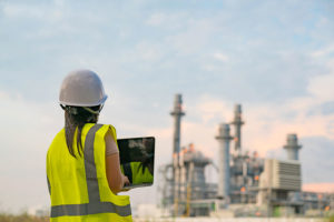 energy sector worker with laptop next to plant