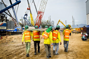 construction workers carrying equipment