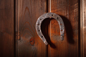 old horse horseshoe hanging horns down on a rusty nail on a dark wooden wall